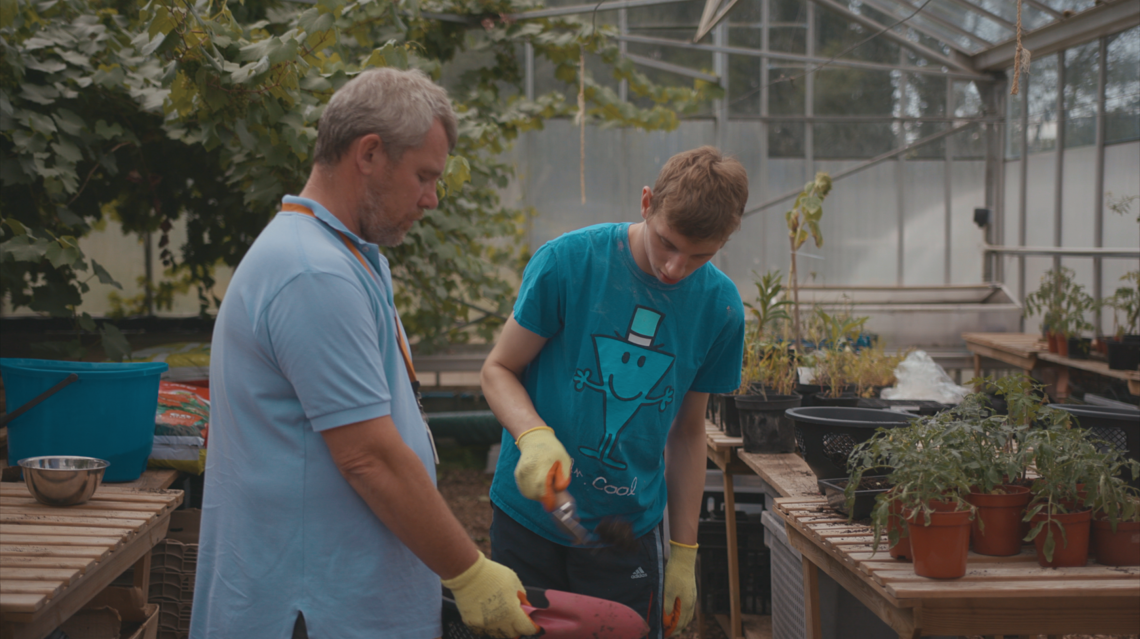Boy and man in a greenhouse potting plants.