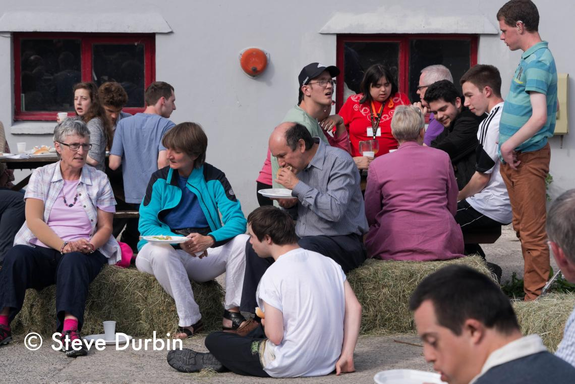 Families sat outside on straw bales at Elidyr Communities Trust.