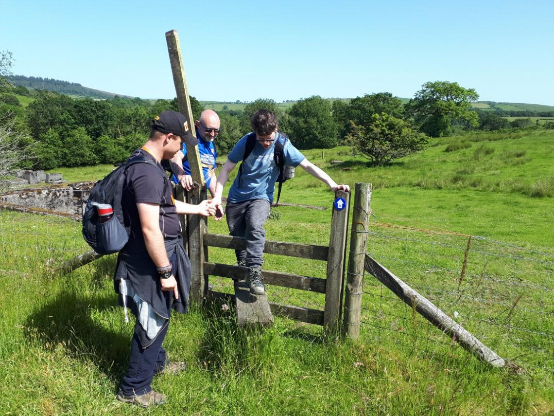 Boy being helped to climb over a stile.
