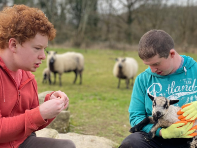 Two boys in a field with lambs at Elidyr Communities Trust.