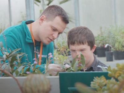 Educator and boy in greenhouse